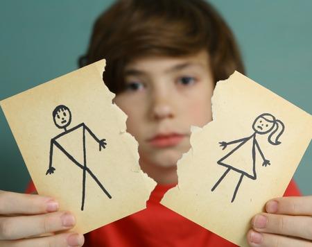 verdrietig preteen jongen ongelukkig over ouders scheiden, houdt man en vrouw papier tekening verscheurd Stockfoto