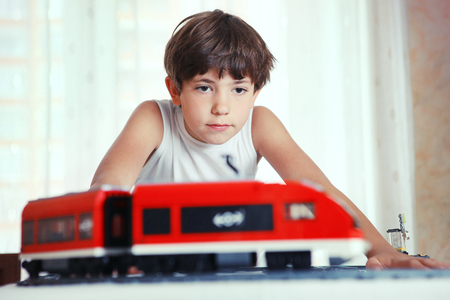 preteen handsome boy play with meccano toy train and railway station Imagens
