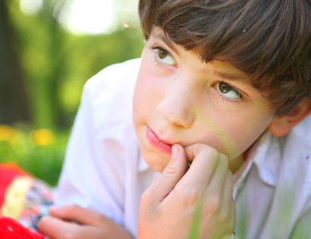preteen handsome boy face close up portrait in the summer park