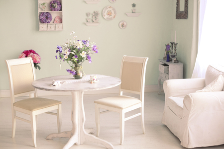 shabby chic dining room interior with flowers decorative plates on wall and tea cup