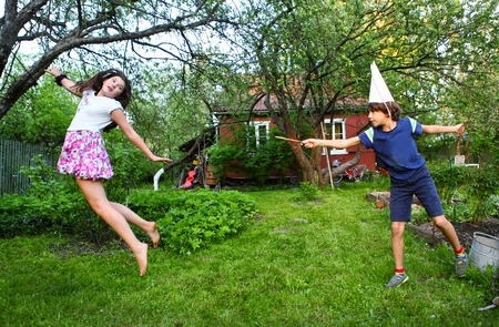 siblings boy and girl play game with magic stick Stock Photo