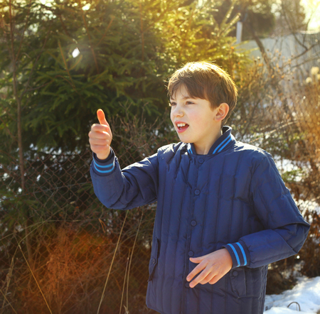 toss: preteen handsome boy toss a coin on the country spring sunny village background