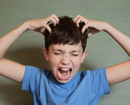 Preadolescente chico guapo rascarse la cabeza aislado en la invasión de pulgas azul Foto de archivo - 72549521