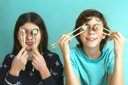 teen siblings boy and girl kids with sushi rolls avocado and salmon close up smiling photo, brother and sister eating sushi rolls
