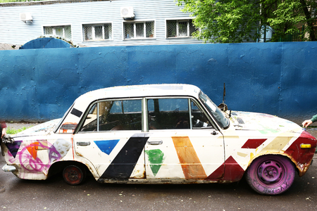 old abandoned car painted with paint spray broken without wheel close up photo Stock Photo