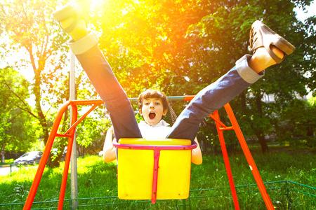boyhood: Cute child, boy, having fun on a swing in the backyard on sunset