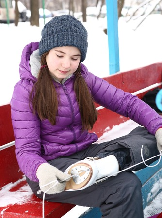 teenager girl put on skate boots on ice rink