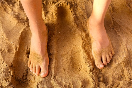 flat foot: kids foot on the beach sand as a therapy against patypodia flat foot