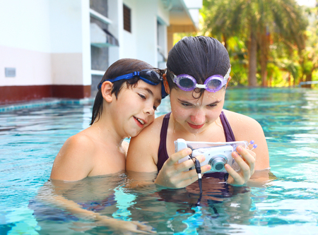 teen siblings boy and girl brother and sister make underwater camera shoot footage in the open air swimming pool in thailand