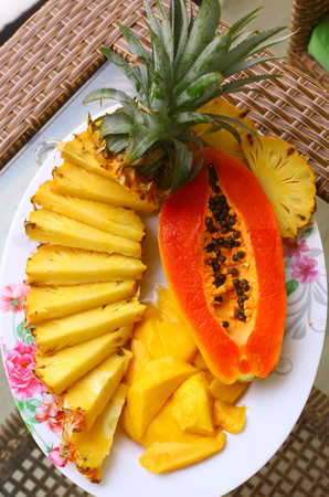 tropical fruit pineapple, mango, corambola, papaya on the plate served on palm tree for dietary light breakfast