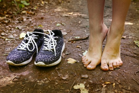bare feet stay tiptoe and trainer shoes close up photo on the forest path Archivio Fotografico