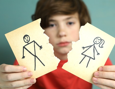 sad preteen boy unhappy about parents divorce, hold man and woman paper drawing torn apart
