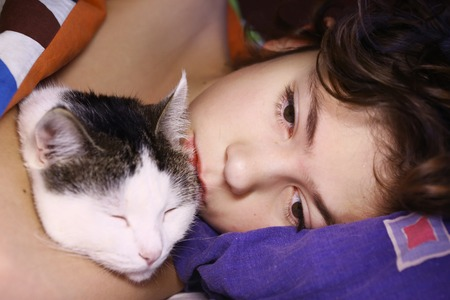 inseparable: preteen handsome boy with cat hugging in bed close up portrait