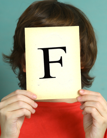 negatively: preteen boy with bad mark F - falure close up photo sad and frustrate