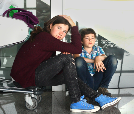 back home: two teen sibling boy and girl brother and sister with trolley in the airport sad waiting for delayed fligt back home Stock Photo