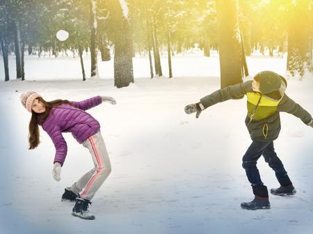 palle di neve: bambini lanciare palle di neve nel parco nevoso inverno vicino foto