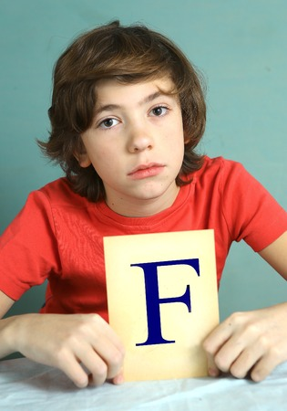 negatively: preteen boy with bad mark F - failure close up photo sad and frustrate