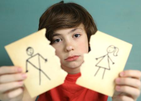 Preteen bel ragazzo tenere mamma e papà disegno disgiunto con triste espressione close up photo