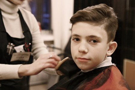 desing: teen handsome boy in barber shop having his hair cut close up photo Stock Photo