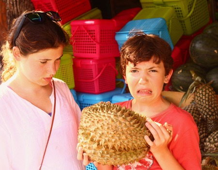 preteen boy smell durian - tropical fruit with good taste but bad smell