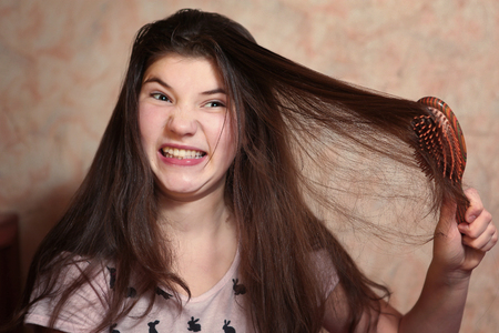 thick hair: beautiful teen girl try comb her long dark thick hair Stock Photo