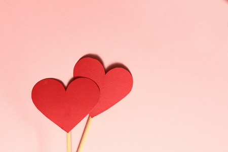 two red paper heart on wooden stick together on the pink background and copy space for valentines day congratulation description