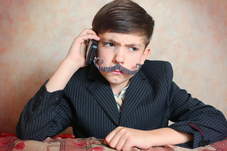 boy in businessman suit and mustage angry Stock Photo