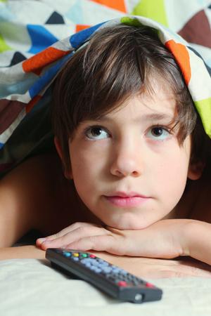 ver tv: preadolescente chico guapo tiene un buen tiempo en la cama a ver la televisión con mando a distancia Foto de archivo