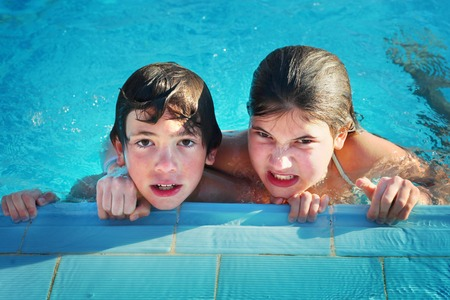 preteen siblings boy and girl in open air  swimming pool in egypt