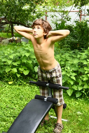 Young boy doing push-ups on a portable trainer outdoors in the countryside as he does his training exercises, frontal view