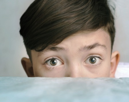 'hide out': teen handsome boy look over the shirm close up portrait