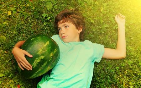 preteen boy have siesta nap with water melon outdoor field portrait