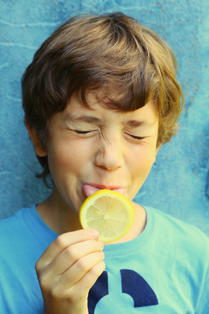 preteen handsome boy eating lemon with sore grimace close up outdoor portrait