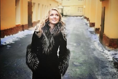 jonge blonde vrouw in zilver vos bontjas outdoor winter straat portret op de besneeuwde achtergrond