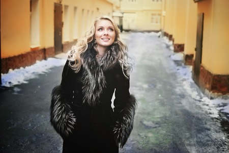 young blond woman in silver fox fur coat outdoor winter street portrait on the snowy background