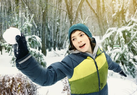 agression: teen boy throwing snow ball outdoor on winter park snowy background Stock Photo