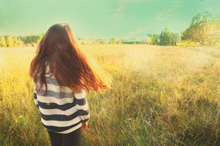 loose hair: teen girl with long brown loose hair stay back on the summer field on sunny day Stock Photo