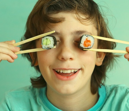 hashi: preteen handsome boy with sushi roll set and stick hungry Stock Photo