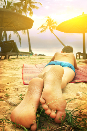 teen boy lay on beach feet out close up photo on sea sunset background