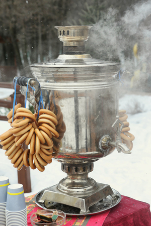 russian samovar cattle boiler with bagel bunch on winter snow background