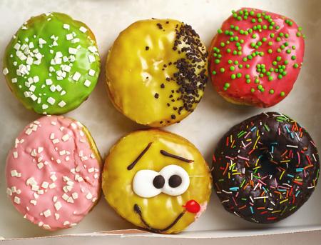 multi colored doughnuts in box close up photo