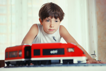 preteen handsome boy play with meccano toy train