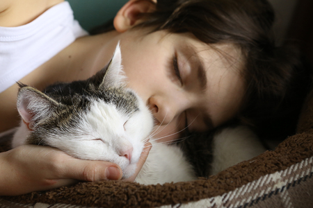 teenager boy sleeping with cat close up portrait