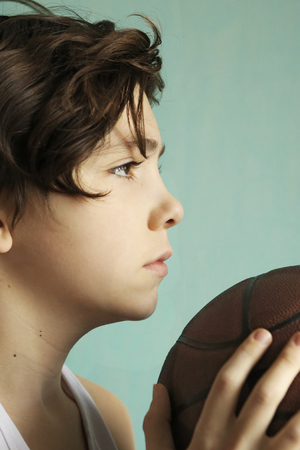 teenager boy with basketball ball close up half face portrait
