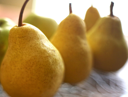 big whole yellow pears close up photo on crystall plate