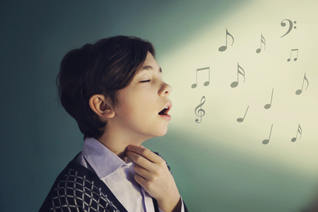 Cantante teenager del ragazzo cantare vicino ritratto su sfondo blu