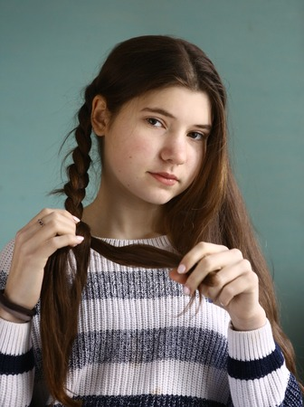 teenager pretty girl plaiting plait long brown hair close up portrait