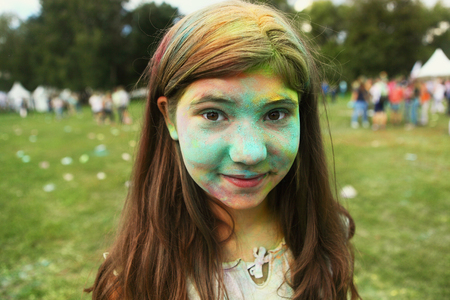 teenager girl with painted face on holi colour fest summer portrait Stock Photo