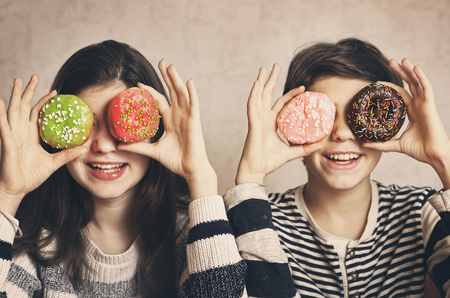 teen siblings boy and girl with doughnuts eyes smiling close up portrait 版權商用圖片