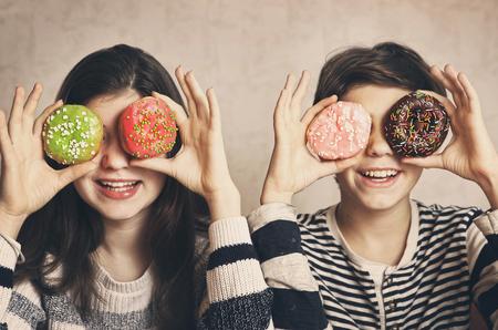 tiener broers en zussen jongen en meisje met donuts ogen glimlachend close-up portret